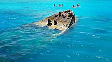 Group of people jet skiing near a shipwreck in the clear turquoise waters of King's Wharf, Bermuda