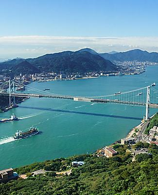Mountain or helicopter view of Kitakyushu, Japan with views of the water, mountains, and a bridge