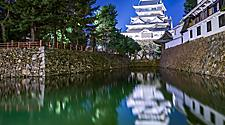View of Kokura Castle with water reflections and trees surrounding