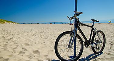 A bicycle resting on a pole at a beach in Klaipeda, Lithuania