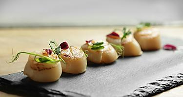 Five scallops on a black plate with garnish