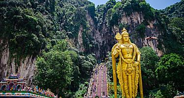 The Batu Caves with a gold statue of Lord Murugan at the entrance near Kuala Lumpur, Malaysia