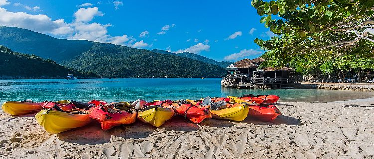 Multiple beach kayaks lined up along the shore of the beach in Labadee, Haiti