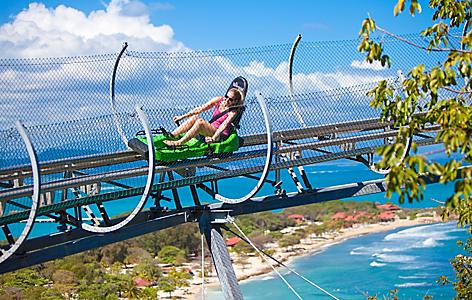 Girl riding Dragon's Tail Coaster with view of the beach, Labadee, Haiti