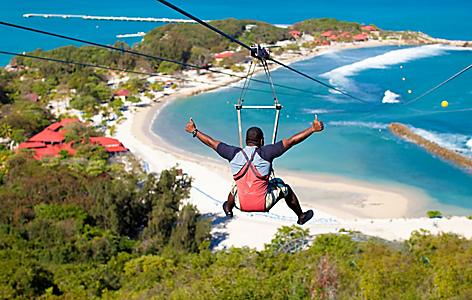 Man zip lining down Dragon's Breath Flight Line with view of the beach below, Labadee, Haiti