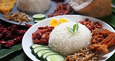 Nasi Lemak is a local cuisine in Langkawi, Malaysia consisting of rice with coconut cream, meats, and veggies