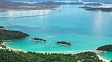 An aerial view of the ocean in Langkawi, Malaysia with mangroves and mountains surrounding it