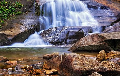 Seven wells waterfall with rocks into a stream of water in Langkawi, Malaysia