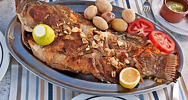 A whole roasted fish on a silver plate