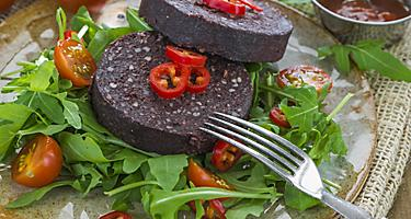 Sliced black pudding on a fresh salad