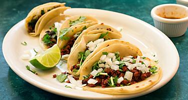 Chorizo tacos on a white plate with a sliced lime