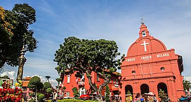 Christ Church Melaka, red church in front of a colorful park in Malacca, Malaysia