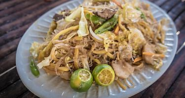 Traditional food in the Philippines with noodles, vegetables, and lime served on the side