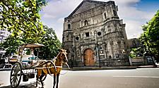 Horse drawn carriage parked in front of a church in Manila, Philippines