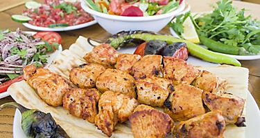 Multiple chicken shish kebobs with a bowl of salad on the side