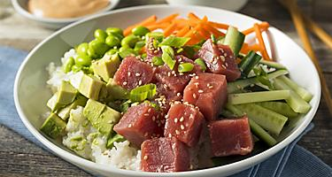 A healthy poke bowl filled with ahi tuna, avocado, veggies, and rice in Hawaii