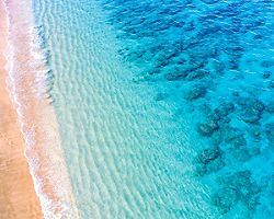 An aerial view of a crystal blue beach and shoreline in Lahaina, Maui, Hawaii