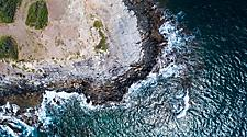 An aerial view of a rocky coastal beach with waves crashing upon rocks in Lahaina, Maui, Hawaii