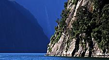 Landscape view of Fiordland National Park with the mountainside meeting the ocean in New Zealand