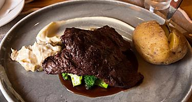 A whale steak with a side potato on a silver plate