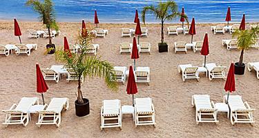 Stylish mediterranean beach with white sunbeds and red umbrellas in Monte Carlo, Monaco