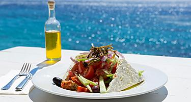 Greek salad and olive oil on sunny seaside restaurant in Mykonos, Greece