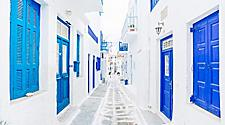 A street of white buildings with blue accents in Mykonos, Greece