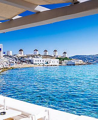 View of the famous Mykonos windmills as seen from a restaurant in Mykonos, Greece