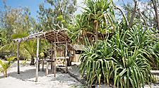 Thatched roof shelter on the beach with tropical plants and trees on Mystery Island, Vanuatu