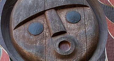 A face carved in wood surrounded by colorful designs