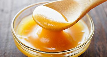 Manuka honey in a bowl with a wooden spoon