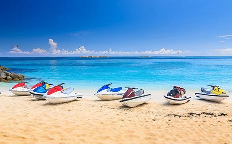 Jetskis lining a white sandy beach in Nassau, Bahamas