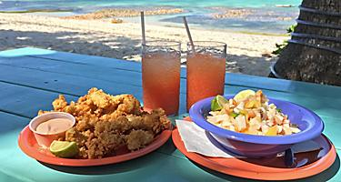 Conch fritters, conch salad, and rum punch on a beachside table