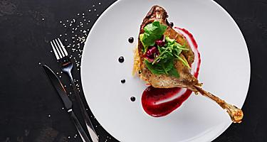 Duck confit with braised cabbage, baked apple and cranberry sauce served on snow white plate with cutlery on black table background