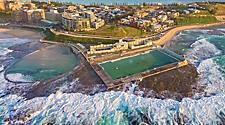 Aerial shot of sun rising over the Newcastle Ocean Baths, NSW, Australia