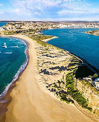 Nobby's beach and lighthouse in an aerial shot of Newcastle, Australia