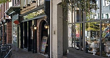 Various storefronts on a brick street