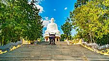 Giant white buddha statue at the top of a wide stair case in a temple in Nha Trang, Vietnam