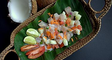 Polynesian authentic and famous dish -raw fish salad with cucumber, lime, tomato and coconut milk