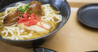 Bowl of Okinawa Soba Soup with thick noodles in Okinawa, Japan