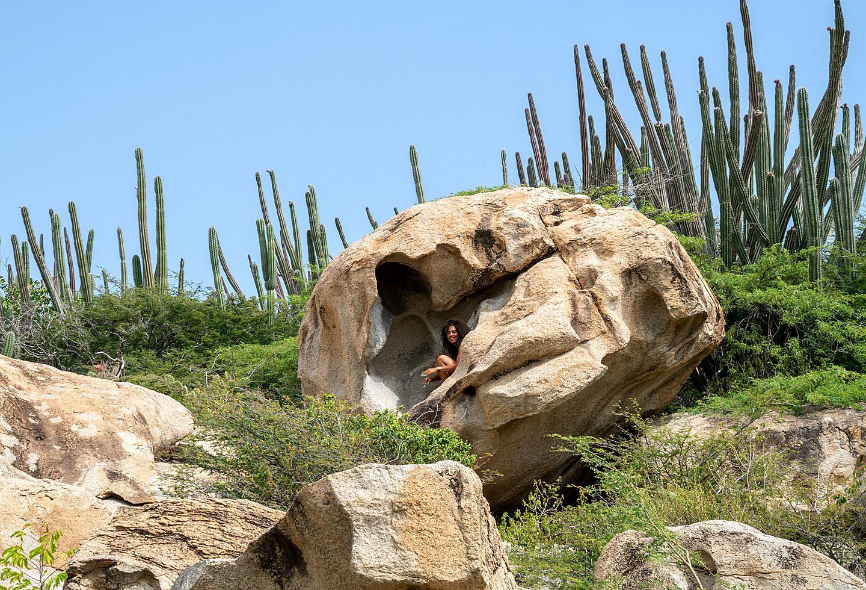 Woman Posing Inside Massive Rock in Aruba