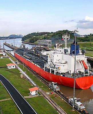 An industrial red ship entering the Panama Canal waterway that connects the Atlantic Ocean to the Pacific Ocean