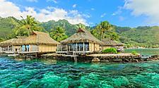 Tiki huts sitting on top of beautiful crystal turquoise waters with mountains in the background in Papeete, Tahiti