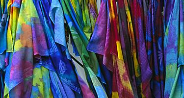 Closeup of colorful Pareus hanging on store rack in Tahiti