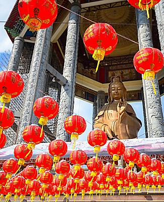Red lanterns hanging from the buddha Guanyin statue in a Chinese temple in Penang, Malaysia
