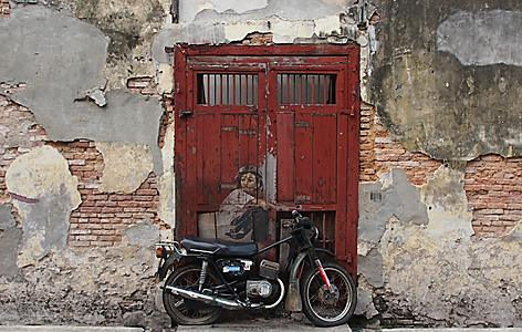 Street art of a boy riding a motorcycle in Penang, Malaysia