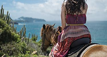 Girl horseback riding with a view of the ocean in Philipsburg, St. Maarten
