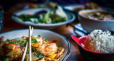 Colorful thai food in bowls with shrimp pad thai and bowls of rice