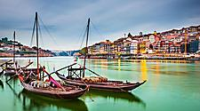Traditional Rabelo boats on the Duoro river, with the cityscape of old town Porto, Portugal