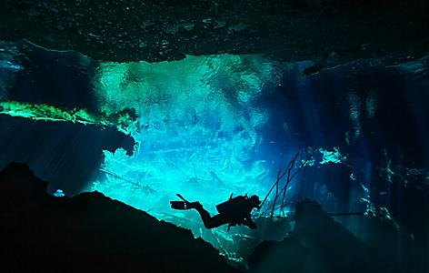 Scuba diver deep in Costa Maya's Cenote Azul